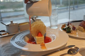 Angel cake dessert being submerged in strawberry consomme at White Modern Aruba